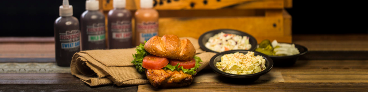 Photograph of a chicken sandwich and a side of mac 'n cheese and coleslaw