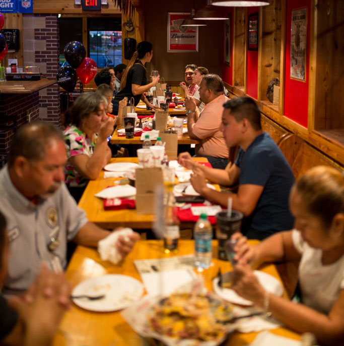 a vertical picture of customers enjoying barbecue at Bar-B-Cutie