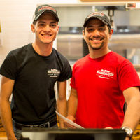 a photograph of two smiling Bar-B-Cutie employees