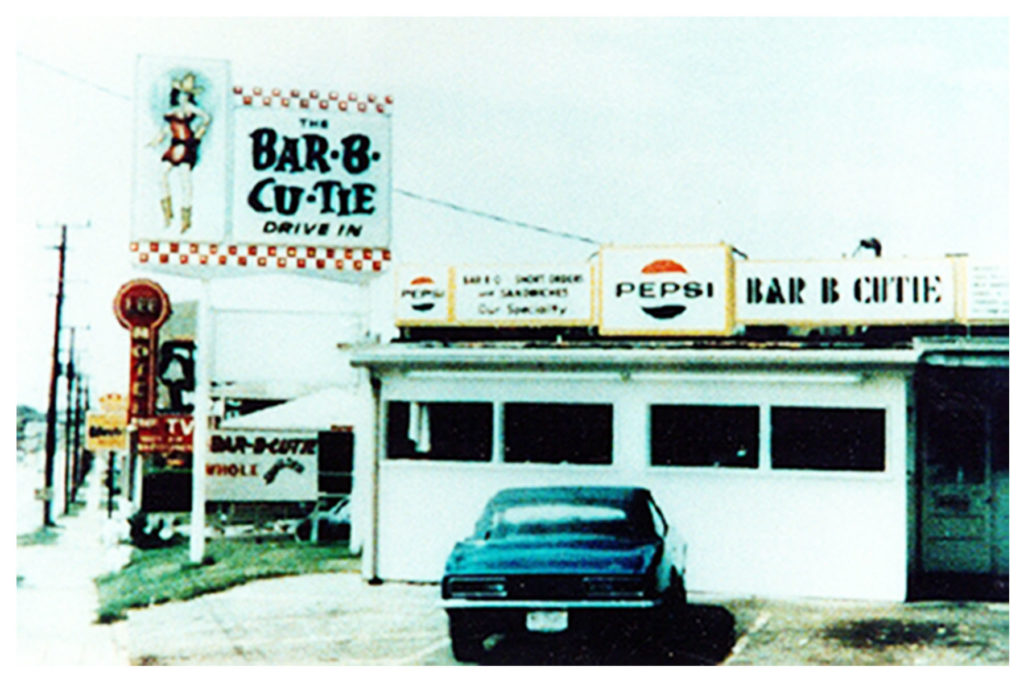 Photograph of a vintage Bar-B-Cutie location: a car is parked in front of a white garage and a sign of a woman in a cowboy hat is next to a vintage pepsi-cola advertisement.