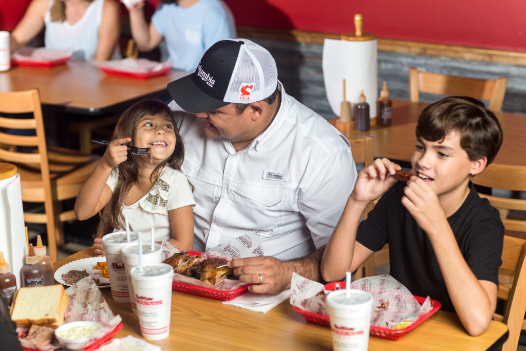 A photograph of a smiling father eats dinner with his two children at Bar-B-Cutie