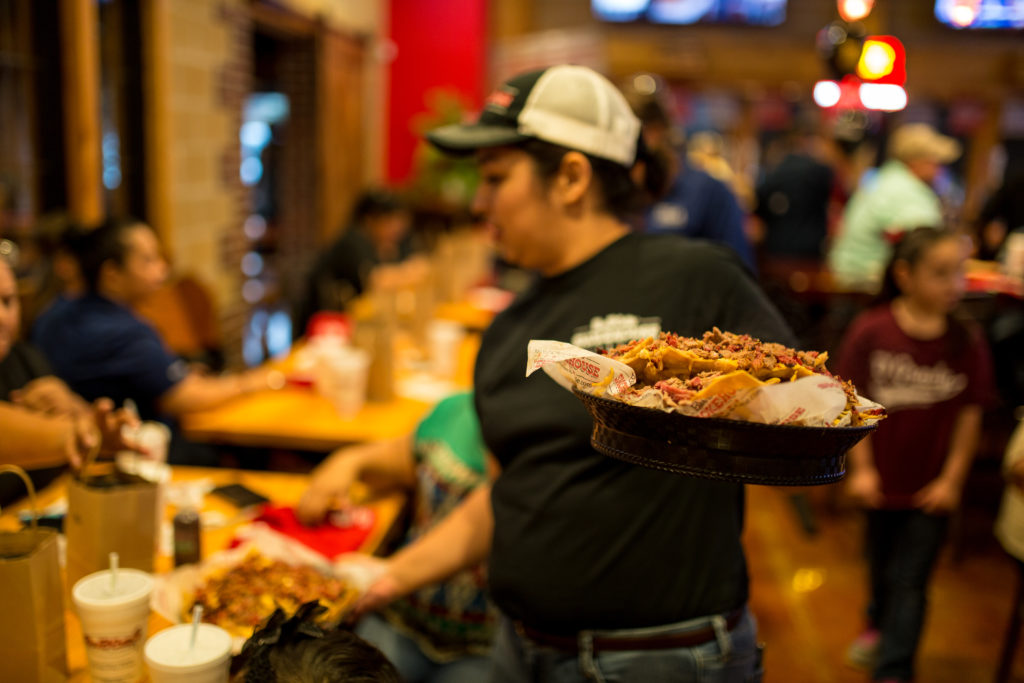 A photograph of a server holding barbecue nachos