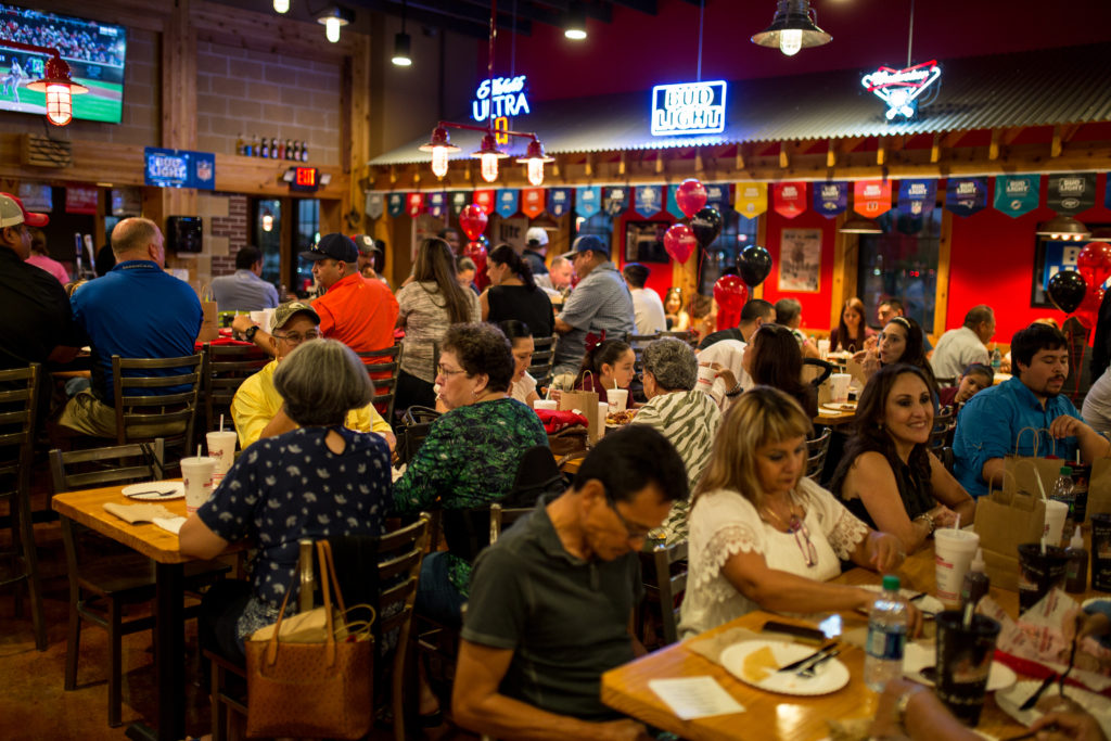 a photograph of a crowded Bar-B-Cutie franchise, people are eating barbecue and drinking beer.