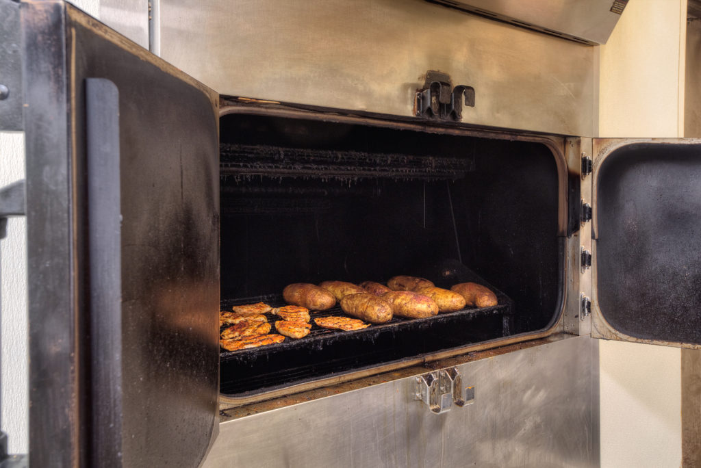 A photograph of a Bar-B-Cutie oven with baked potatoes and barbecue chicken