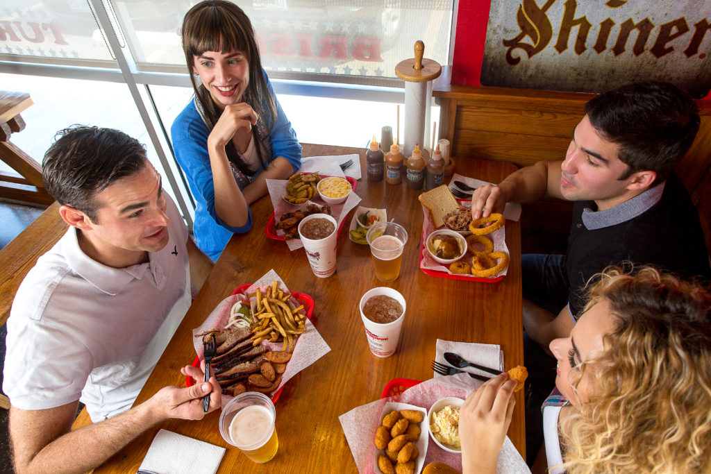 Photograph of smiling people at a table eating brisket and bar-b-cutie sandwiches