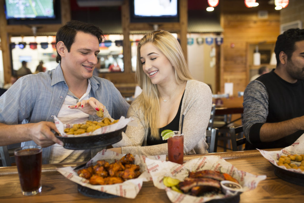 A photograph of a smiling couple eating fried pickles