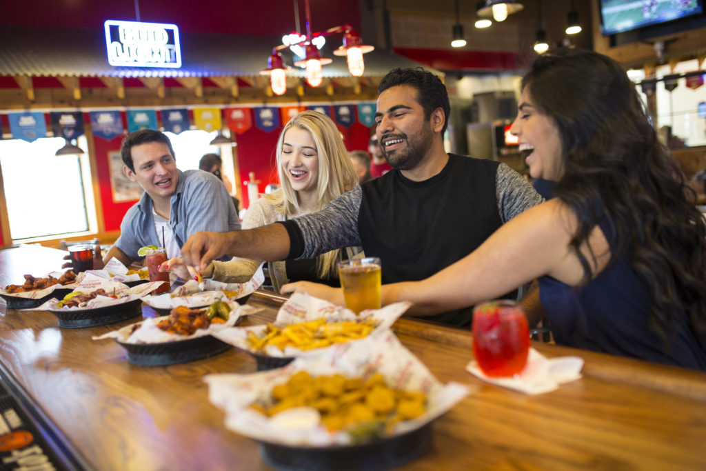 Photograph of two women and two men eating fried food while drinking cocktails and beer inside a Bar-B-Cutie location.