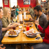 A photograph of a happy group of people drinking and eating barbecue nachos