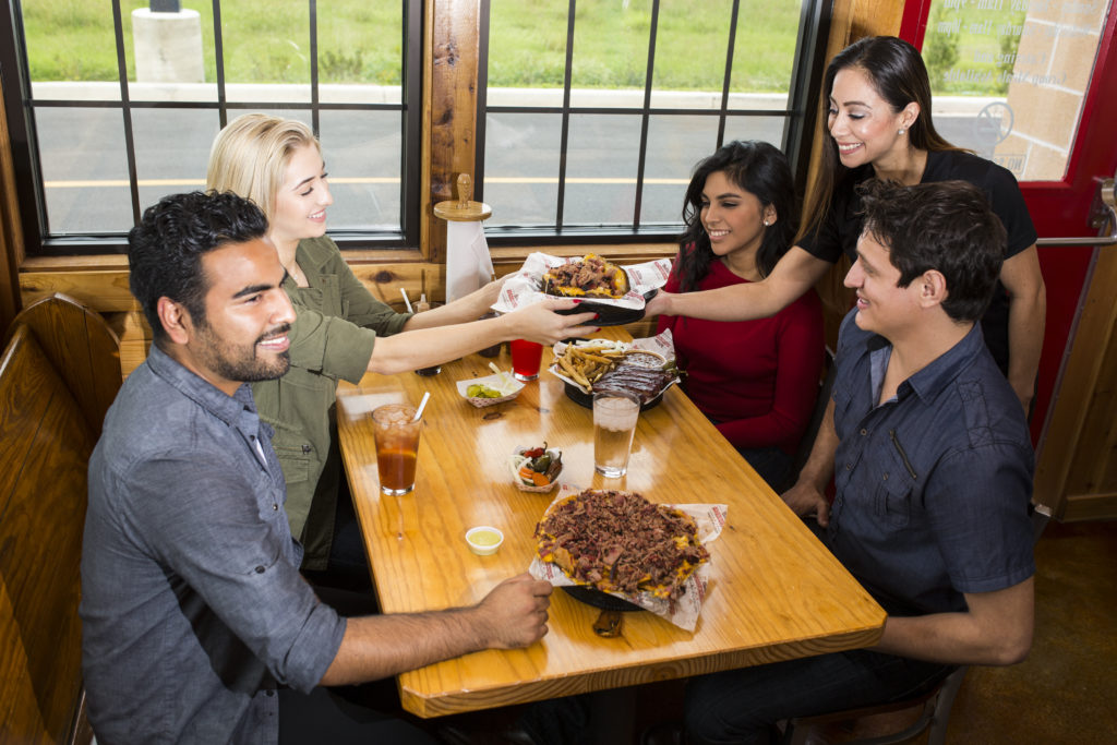 A smiling group of people eat Barbecue at a wooden table