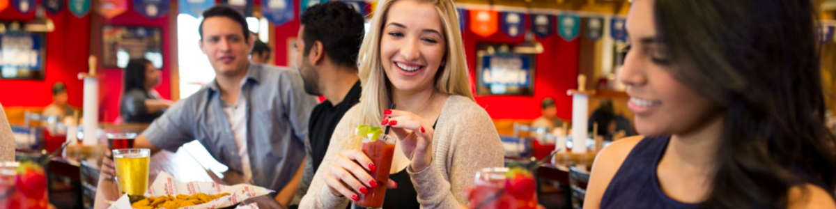 a smiling woman drinking cocktails with her friends