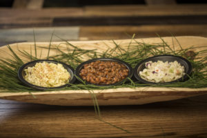 a photograph of side dishes (mac n' cheese, baked beans, coleslaw) in a wood bowl