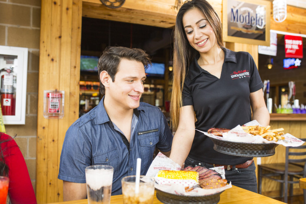 photograph of smiling server serving brisket and corn to a customer