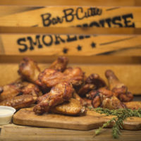 close-up photograph of barbecue chicken wings, ranch, and rosemary sprigs